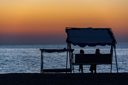 Silhouette of two people on a patio swing with canopy on the beach admiring the sunset on the sea Standard-Bild - 138038332