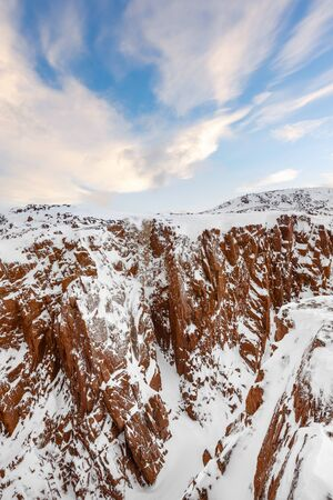 Snow covered red rocks on the Barents Sea in Teriberka, Kola peninsula, Russia. A remote, but famous tourist destination above the Arctic Circle Stock Photo