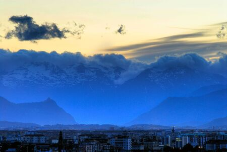 View of Turin (Torino) Italy at sunset looking toward Susa Valley with the backdrop of the Italian Alps and the Sacra di San Michele Church silhouetted Stock Photo