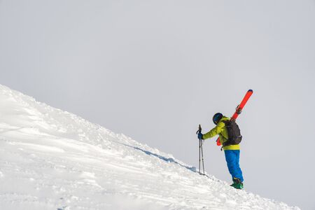 Skier climbing a mountain on foot while carrying his skies ready for some off-piste. The overcast sky makes for a perfect neutral background with ample space for text