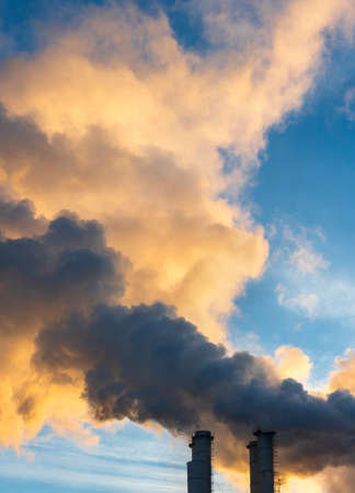 Industrial chimneys spewing smoke and soot in the blue sky polluting the air and causing global warming and climate change with greenhouse gasses and CO2 emissions