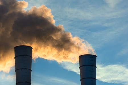Industrial chimneys spewing smoke and soot in the blue sky polluting the air and causing global warming and climate change with greenhouse gasses and CO2 emissions Reklamní fotografie