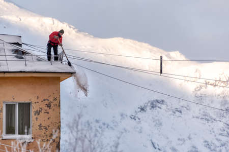 Kirovsk (Murmansk), Russia - 02 12 2019: a man removes excess snow from the roof of a house with a shovel against the backdrop of the Khibiny Mountains