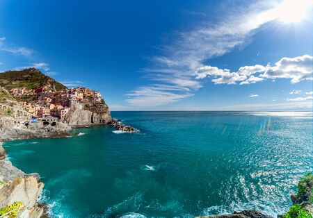 Manarola, one of the five villages of Cinque Terre in Italy on the Liguria Coast on the Mediterranean sea in a sunny summer day with lens flare creating rainbow colored sun rays