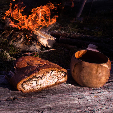 pasty: Fish pasty and coffee at a campfire