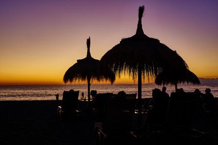 Straw beach umbrella at sunset on spanish beach