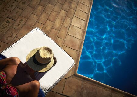woman sunbathing next to pool wearing hat over her face
