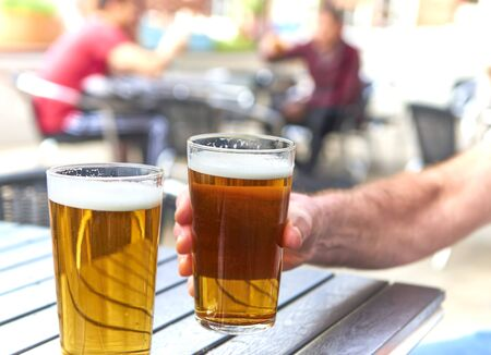 male hand  holding beer glass at table out doors out of focus drinkers in background