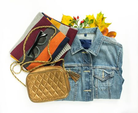 Stylish autumn look. Autumn fashion, woman autumn outfit on white background. Blue denim jacket , retro sunglasses, bronze crossbody bag, stripe scarf. Flat lay, top view
