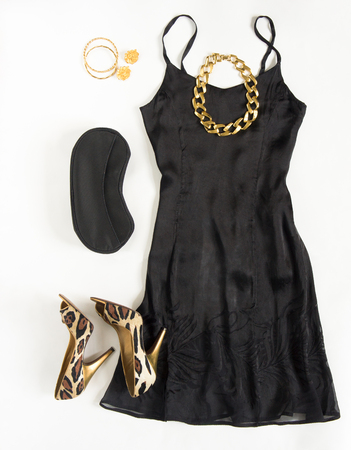 party outfit: Christmas party outfit. Cocktail dress outfit, night out look on white background. Little black dress, black clutch, leopard shoes, gold necklace, bracelets and earrings. Flat lay, top view