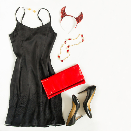 Christmas party outfit. Cocktail dress outfit, night out look on white background. Little black dress, red evening clutch , black shoes, red ang gold necklace and devil horns. Flat lay, top view Stock Photo - 68939534