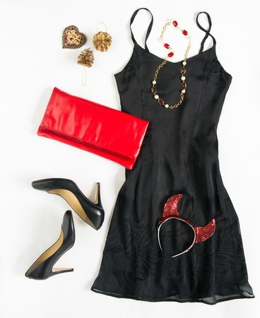 party outfit: Christmas party outfit. Cocktail dress outfit, night out look on white background. Little black dress, red evening clutch , black shoes, red ang gold necklace and carnaval devil horns. Flat lay, top view
