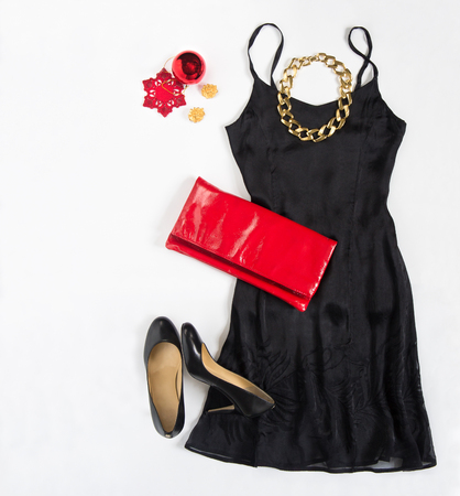 party outfit: Christmas party outfit. Cocktail dress outfit, night out look on white background. Little black dress, red evening clutch , black shoes, red ang gold necklace. Flat lay, top view