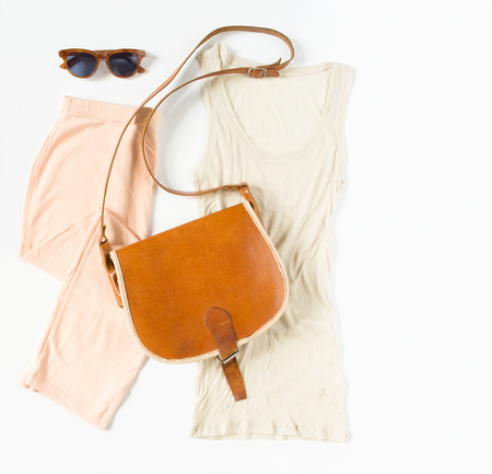 Stylish female clothes set. Womangirl outfit on white background. Peach skirt, nude tank, vintage crossbag and retro sunglasses. Flat lay, top view Imagens