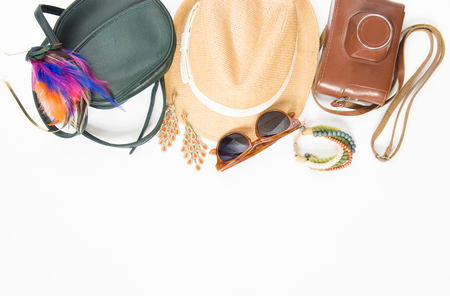stuff: Holidaytravel background. Hipster stuff. Green cross bag, straw hat, retro brown sunglasses, colorful headband, retro camera, boho bracelet and earrings. Flat lay, top view.