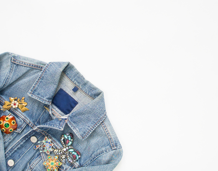 Jeans denim woman jacket with vintage brooches on white background. Fashion outfit