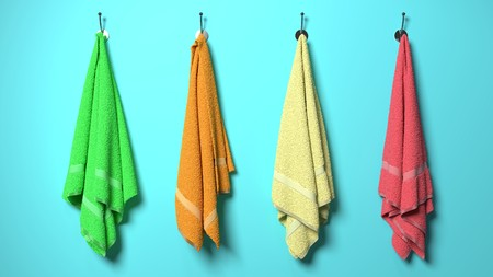 Four soft cotton, fluffy,colorful, green, orange, yellow and red towels hanging on a sea light blue wall, symbolize health, spa and massage, happiness, beach and vacation Stock Photo - 100132015