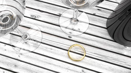 Golden ring for a chosen one, engagement or marriage proposal, expensive golden ring on a wooden table, two glasses and a bottle of red wine Stock Photo