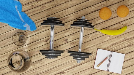 Workout, staying fit and healthy -  two shiny metal dumbells, two oranges and a banana, blue towel, small notebook and a pen, glass of water on a wooden floor