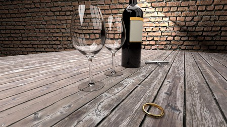 Prepartion for a marriage proposal in a pub or cozy restaurant - golden ring with diamonds, bottle of red wine, two glasses on a dark wooden table and brick wall in the background Stock Photo