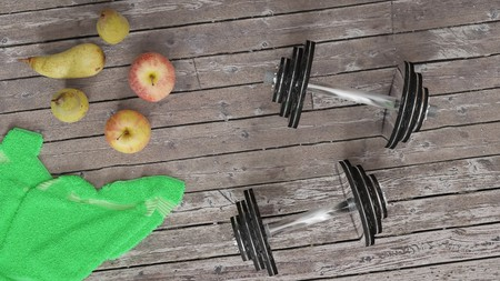 Daily training, staying active and healthy lifestyle symbolized by two shiny metal dumbells, two apples and pears, green towel on a wooden floor