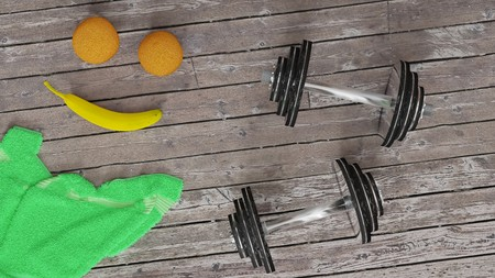 Healthy lifestyle, daily routine of staying fit and  morning exercise  - two shiny metal dumbells, two oranges and a banana, green towel on a wooden floor