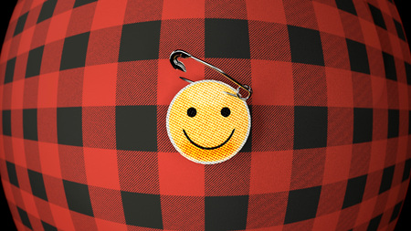 Flannel shirt and smiley clothes badge - two iconic objects, red and black flannel shirt, twisted and bent, and a yellow cloth smiley badge pinned withe a metal safety pin.