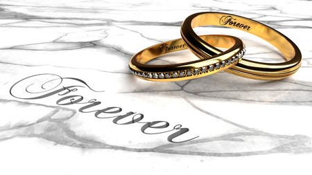 Happy marriage, love forever, together eternally symbolized by two expensive, joined together, inseparable wedding rings with engraved word forever on a white marble table, close up Reklamní fotografie