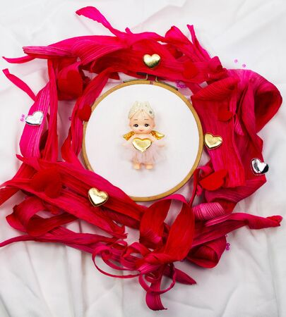 natural materials: Cupid on the center in to surround with red of natural materials Stock Photo