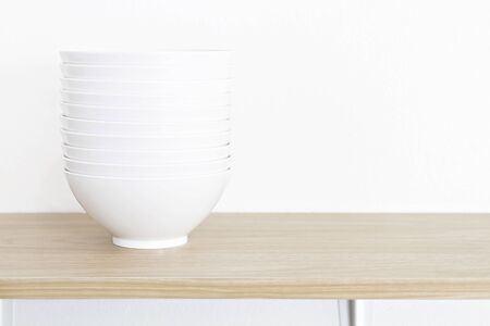 Stack of white bowls on wooden table and white background.