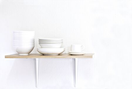Stack of white bowls, plate and cup on wooden table and white background.