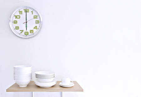 Stack of white bowls, plate and cup on wooden table and white background with clock. Stock Photo