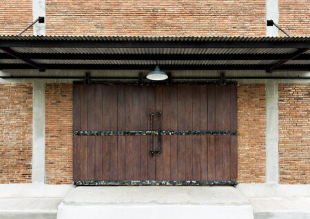 Old wooden door texture plank in a wall traditional brickwork exterior of building with roof.