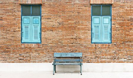 windows frame: Wooden window shutter and chair iron color cyan with traditional brickwork exterior wall.