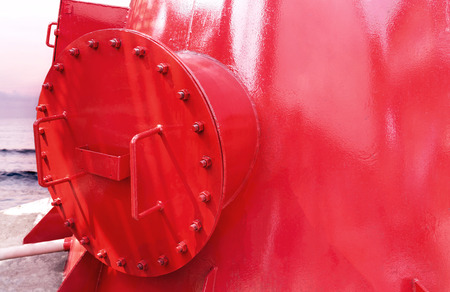 Steel fuel pipes red color with fittings joint with screws and nuts for oil and gas pipeline a the sea background.
