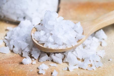 Cristaux blancs de sel de mer sur cuillère en bois isolé sur fond de pierre orange. Banque d'images