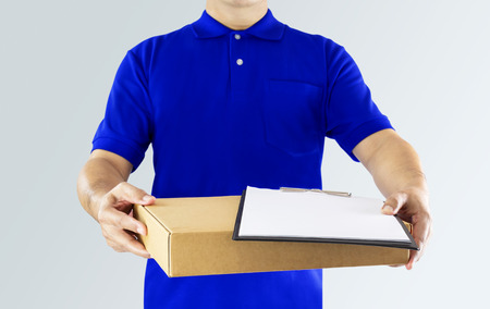 Delivery man in blue uniform and holding blank clipping board with delivering package on gray background. Concept fast delivery service or order online shopping and express delivery.