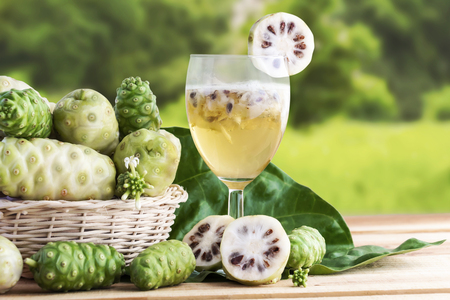 Noni fruit or Morinda Citrifolia with noni juice and leaf in the basket for health on the wooden table background with copy space for text.