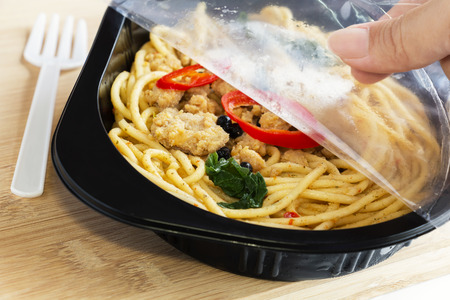 Food Delivery service: Woman hands holding open cling wrap and take out food in plastic boxes on wood background. concept online order take away food ready for home delivery. Standard-Bild