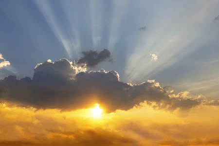 Clouds and sun shines through rays of light in the illuminated picturesque sky. 스톡 콘텐츠
