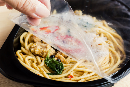 Food Delivery service: Woman hands holding open cling wrap and take out food in plastic boxes on wood background. concept online order take away food ready for home delivery.