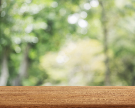 Empty wooden table template top on nature green blurred background for montage of your product on table. Stock Photo