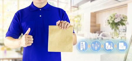 Mano del hombre de entrega que sostiene la bolsa de papel en uniforme azul y medios de comunicación de icono para entregar el pedido de paquete, servicio de entrega de comida rápida en línea en motocicleta o entrega urgente en el fondo de la cafetería. Foto de archivo