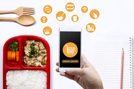 Food delivery service for order online and icon media. Woman hand holding smart phone for ordering food onscreen. Business and technology for shopping online with lifestyle in city concept.