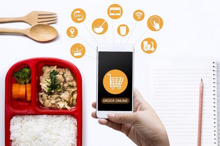 Usługa dostawy jedzenia na zamówienie online i media ikonowe. Kobieta ręka trzyma inteligentny telefon do zamawiania jedzenia na ekranie. Biznes i technologia zakupów online ze stylem życia w koncepcji miasta. Zdjęcie Seryjne