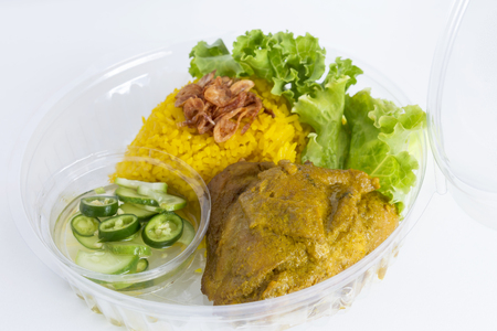 Food Delivery service: Chicken Biryani (Muslim yellow rice with chicken) opening cling wrap and take out food in plastic box. Online order food ready eating for takeaway home delivery concept.