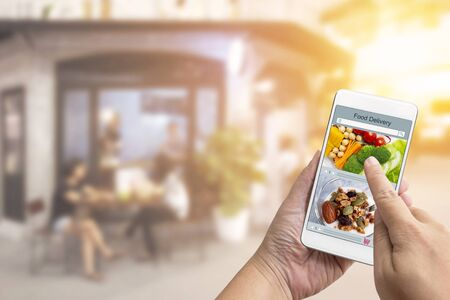 Online order Food shopping concept on touch screen on woman hand. Food delivery service express that is cooked by restaurant and icon symbol media. Business and technology with lifestyle in city.
