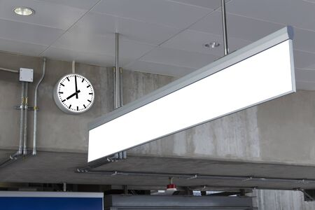 Public clock and blank sign board for information in railway station at the hanging with roof of subway central train station. It is clock for watch time waiting train. Travel and time concept. Banque d'images - 129497598