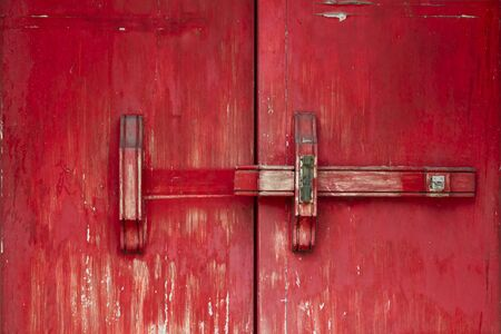 Red vintage wooden door made to plank peeling paint and large locked old wooden with padlock rusty.