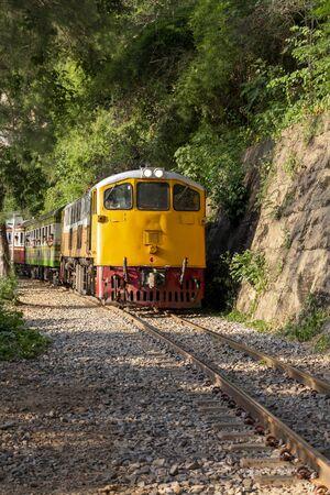 Train touristique voyageant sur la piste historique passe à travers la montagne et la nature tropicale.